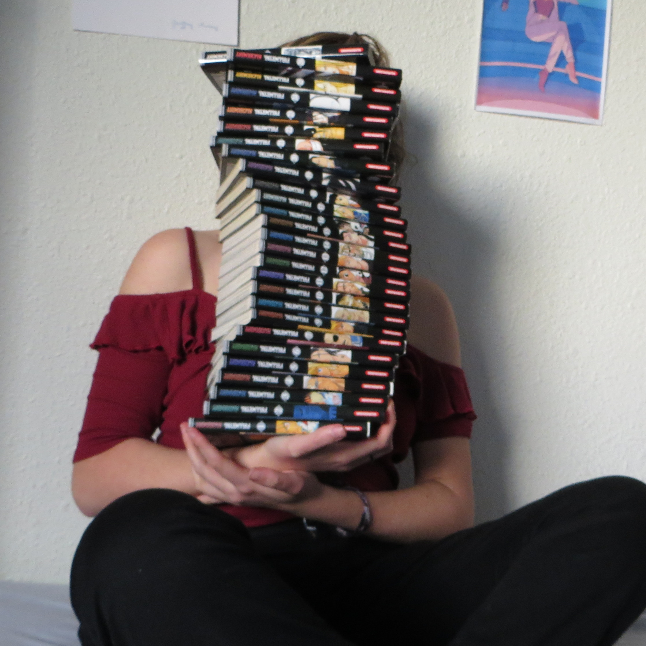 personne tenant la pile des tomes de Fullmetal Alchemist de Hiromu Arakawa