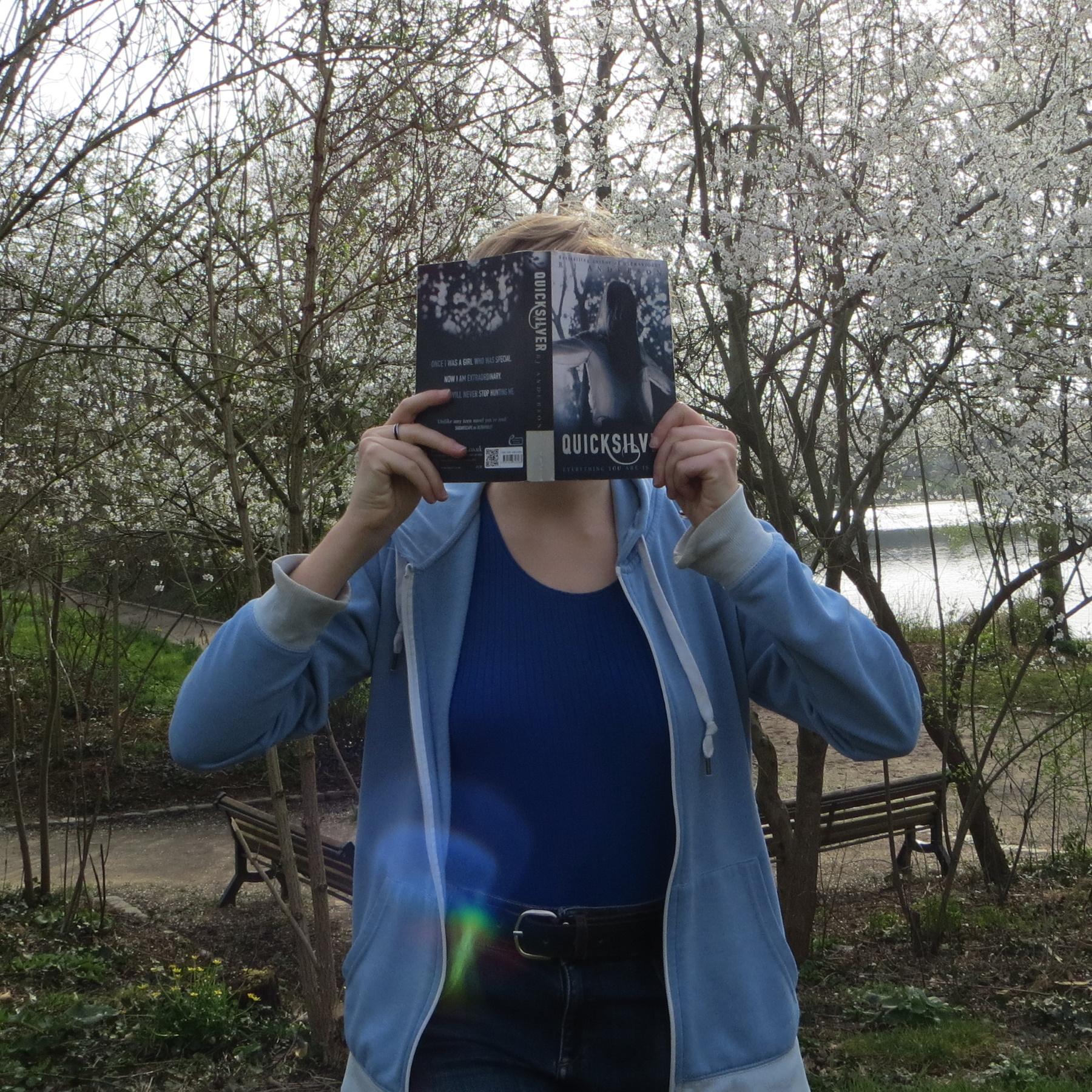 personne en gilet et débardeur bleus lisant Quicksilver de R.J. Anderson devant des arbres aux fleurs blanches