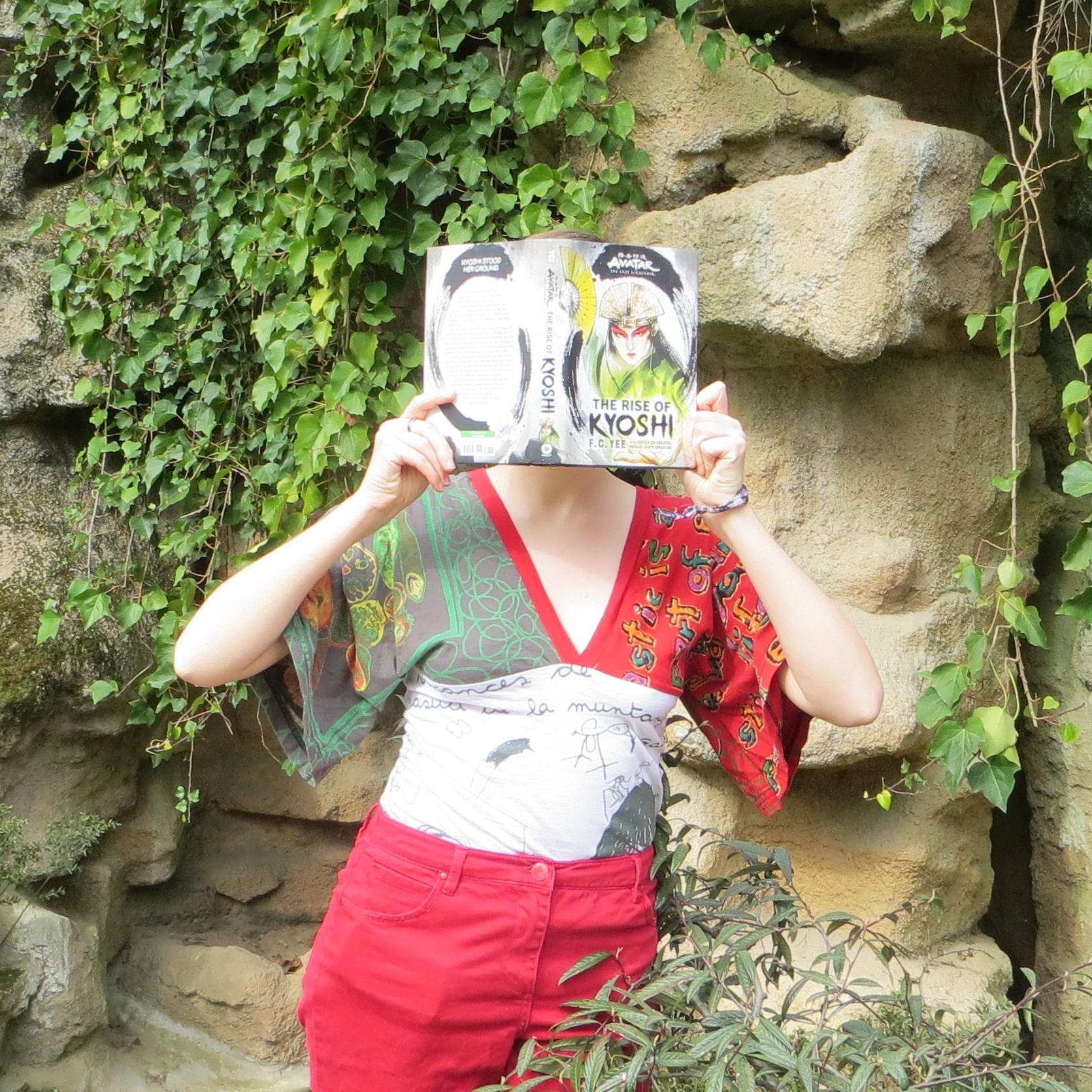 personne en chemisier vert et rouge lisant The Rise of Kyoshi de F.C. Yee devant des rochers percés de grottes