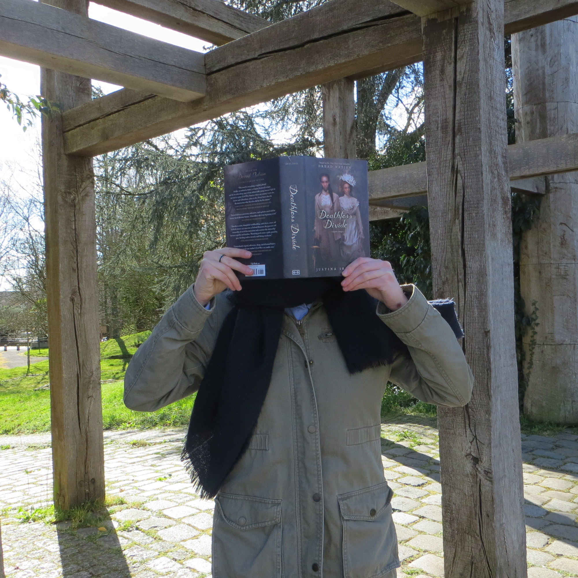 personne en parka vert kaki lisant Deathless Divide de Justina Ireland devant une structure en bois