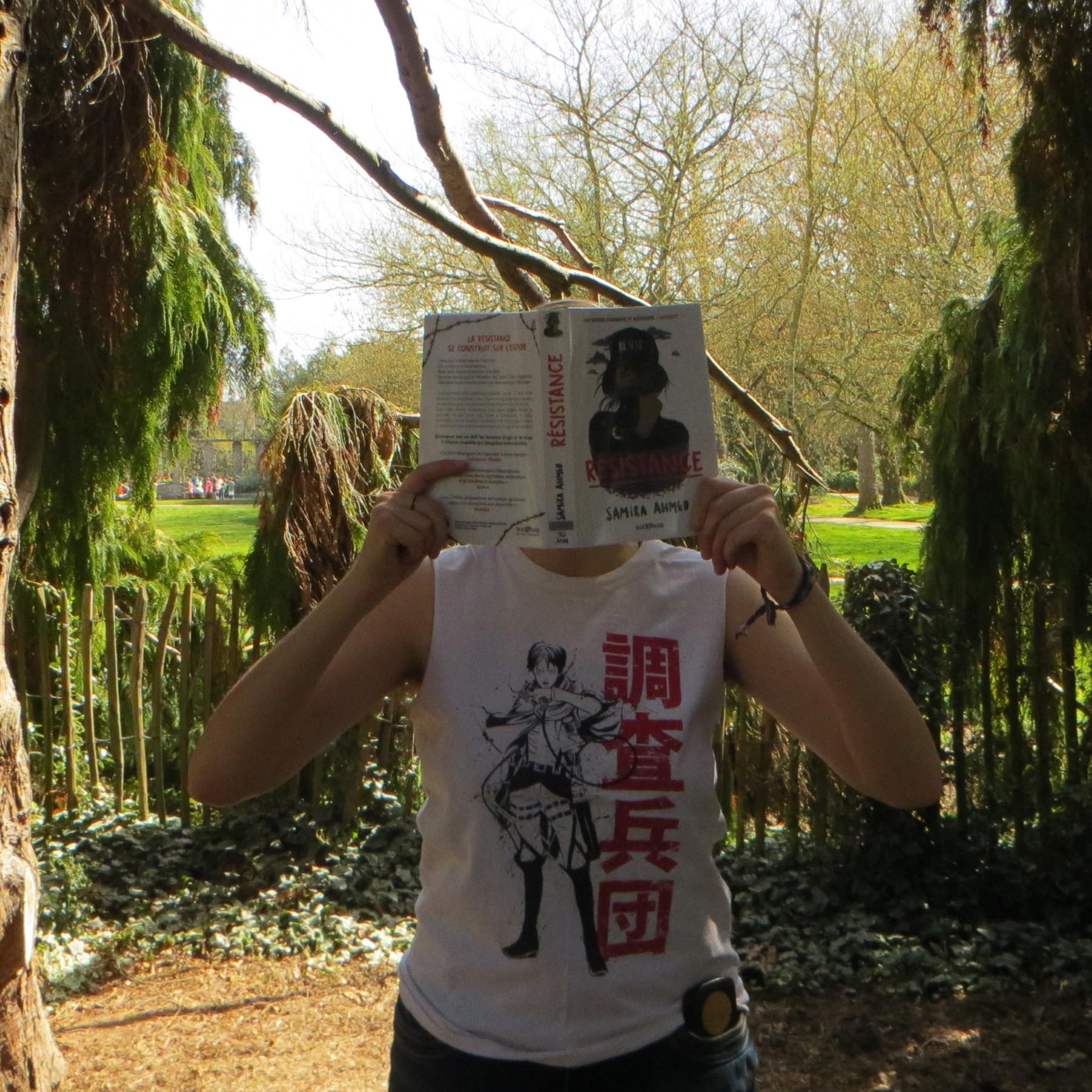 personne en débardeur de l'Attaque des Titans lisant Résistance de Samira Ahmed devant une barrière végétale