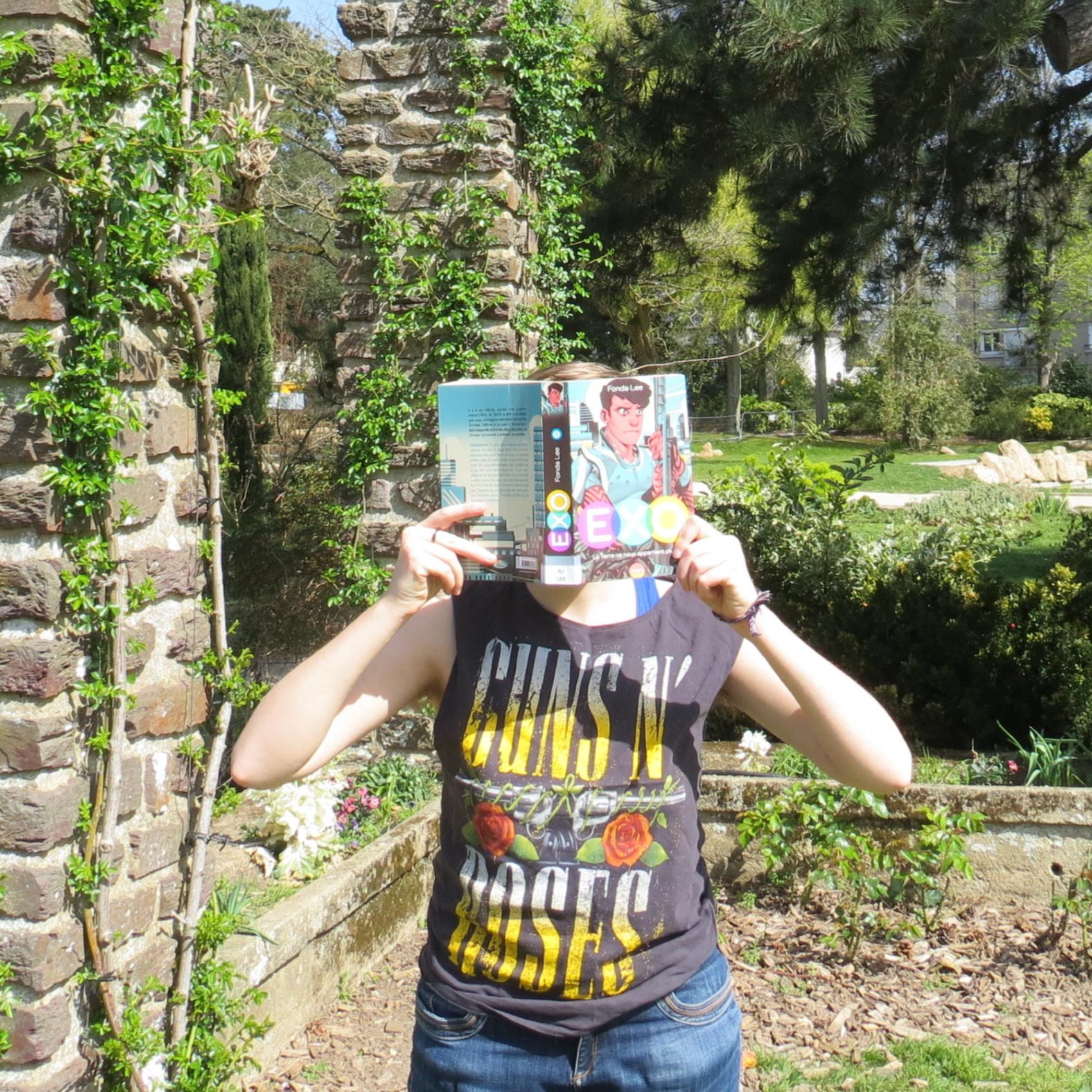 personne lisant Exo de Fonda Lee devant des piliers de pierre et de verdure