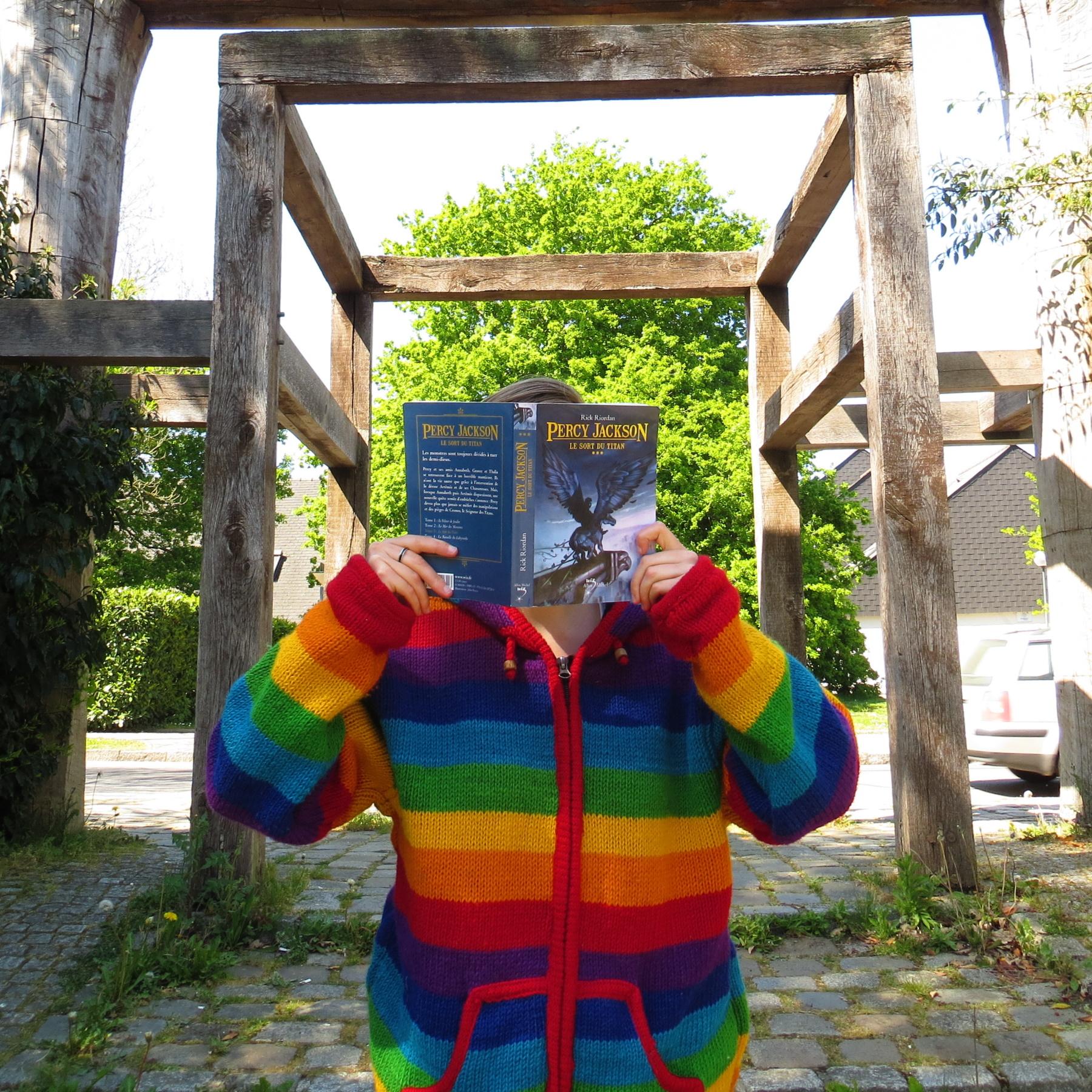 personne en manteau à rayures arc-en-ciel lisant Percy Jackson tome 3 de Rick Riordan devant une structure de bois