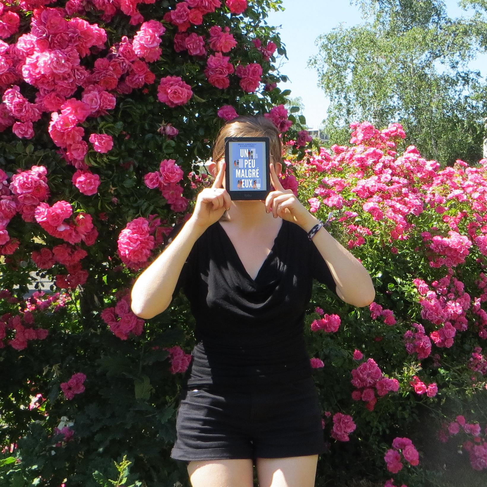personne en tenue noire tenant une liseuse avec la couverture de Un Peu Malgré Eux de Becky Albertalli & Aisha Saeed, devant des buissons de roses