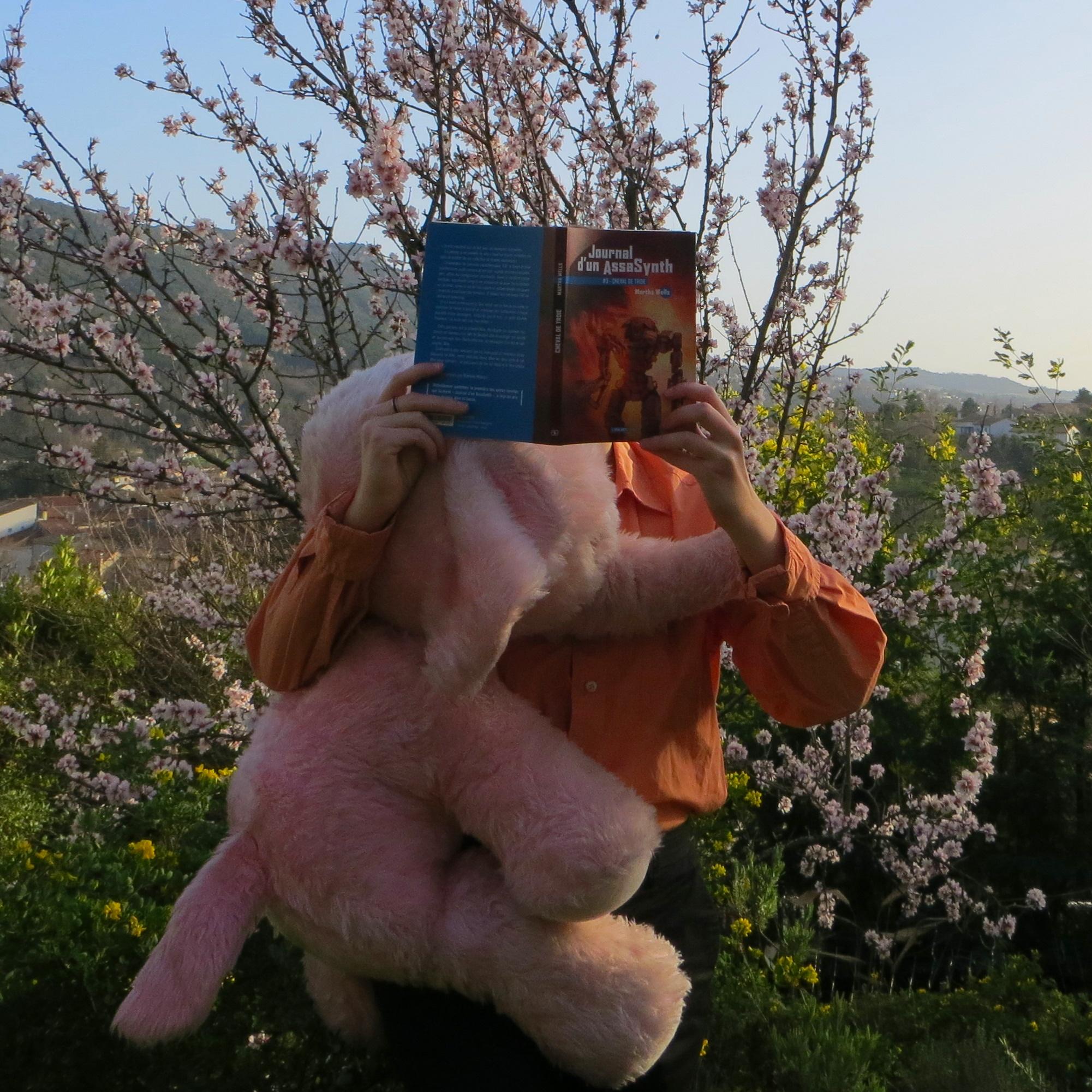 personne en chemise orange lisant Journal d'un AssaSynth 3 : Cheval de Troie de Martha Wells devant un amandier en fleurs, avec une énorme peluche d'éléphant rose dans les bras