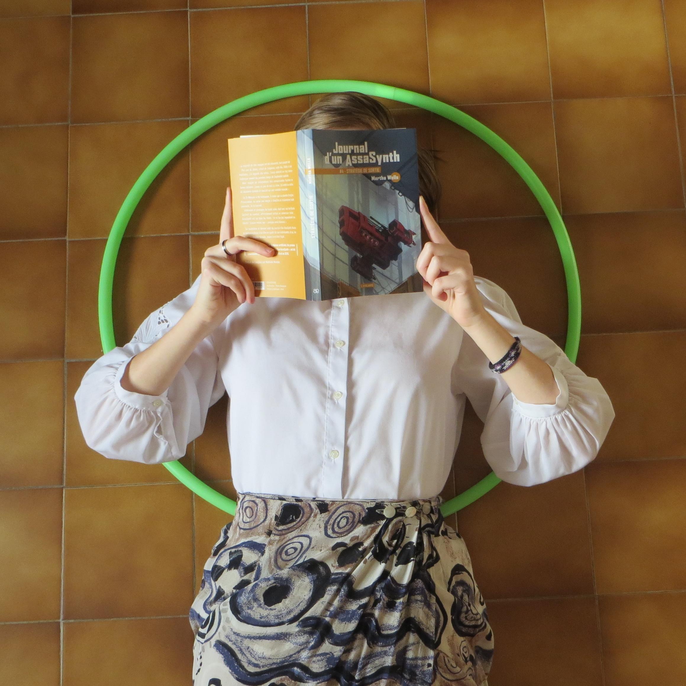 personne allongée sur un carrelage brun, dans un cerceau, vêtue d'une jupe décorée de cercles, lisant Journal d'un AssaSynth tome 4 de Martha Wells, Stratégie de Sortie