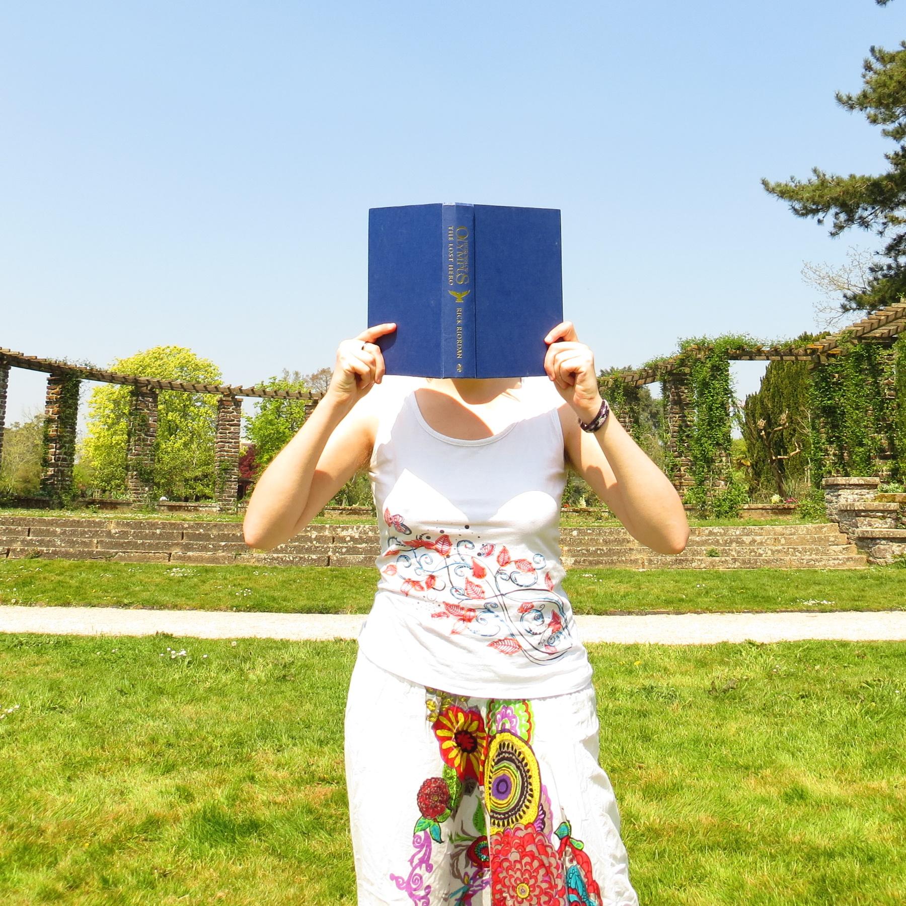 personne en sarouel blanc à motifs colorés lisant Héros de l'Olympe tome 1 devant un demi-cercle de colonnes