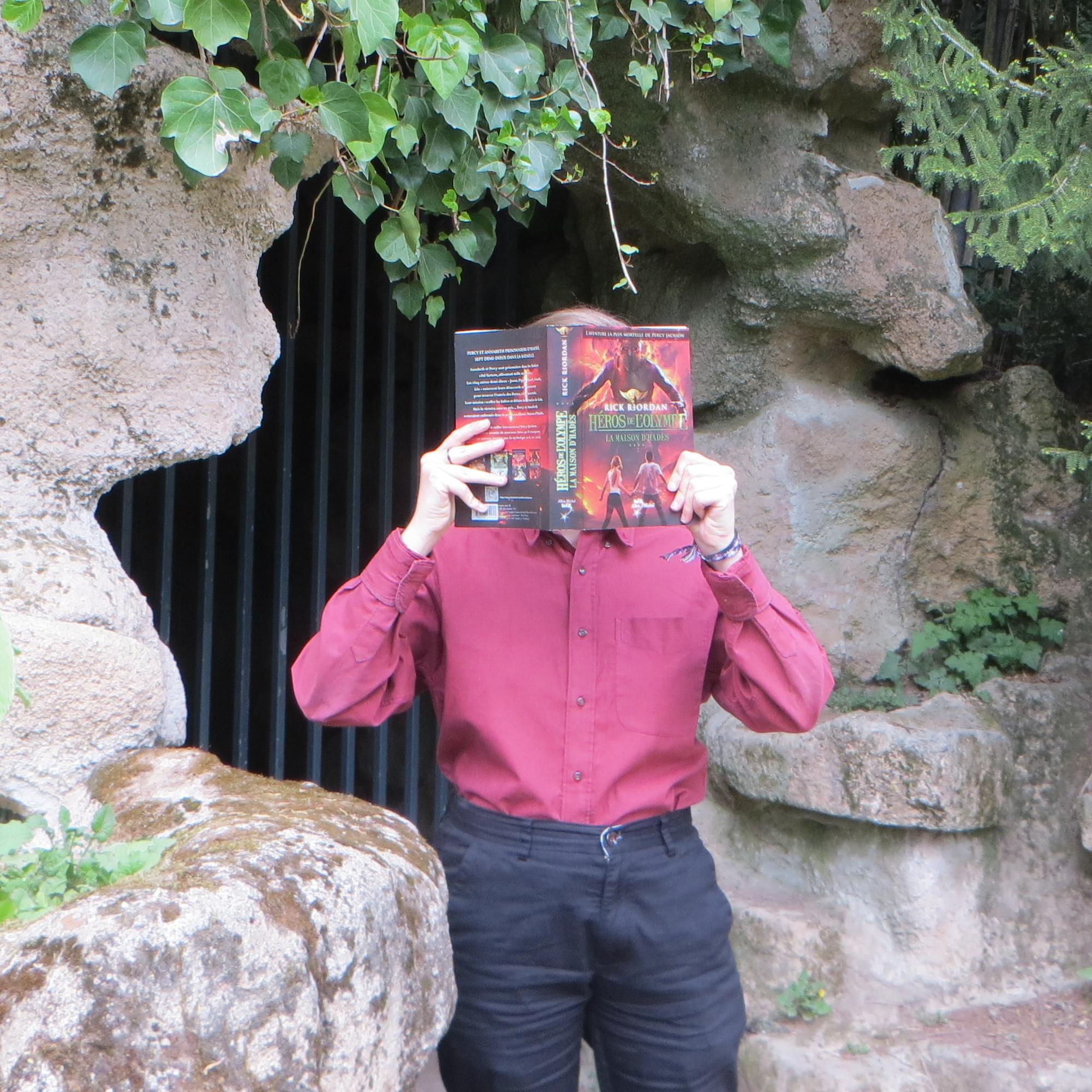 personne en chemise rouge sombre lisant Héros de l'Olympe tome 3 devant une grotte fermée de barreaux