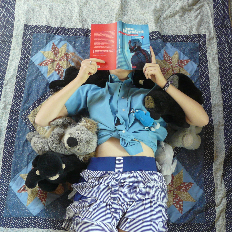 personne lisant Journal d'un AssaSynth 1 : défaillances systèmes de Martha Wells allongée sur une couverture piquetée d'étoiles, entourée de peluches
