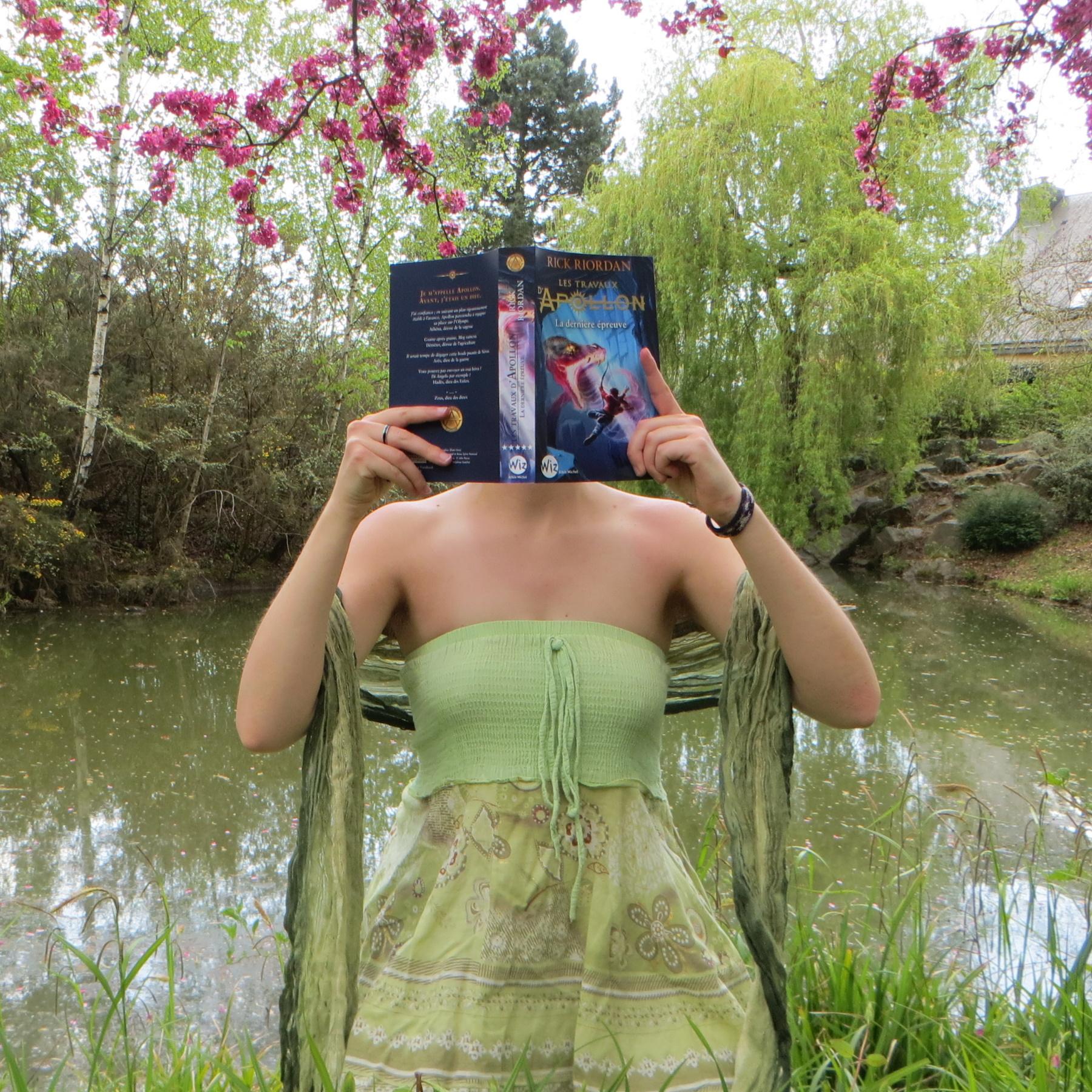personne en robe verte lisant Les Travaux d'Apollon tome 5 : La Dernière Epreuve devant un lac