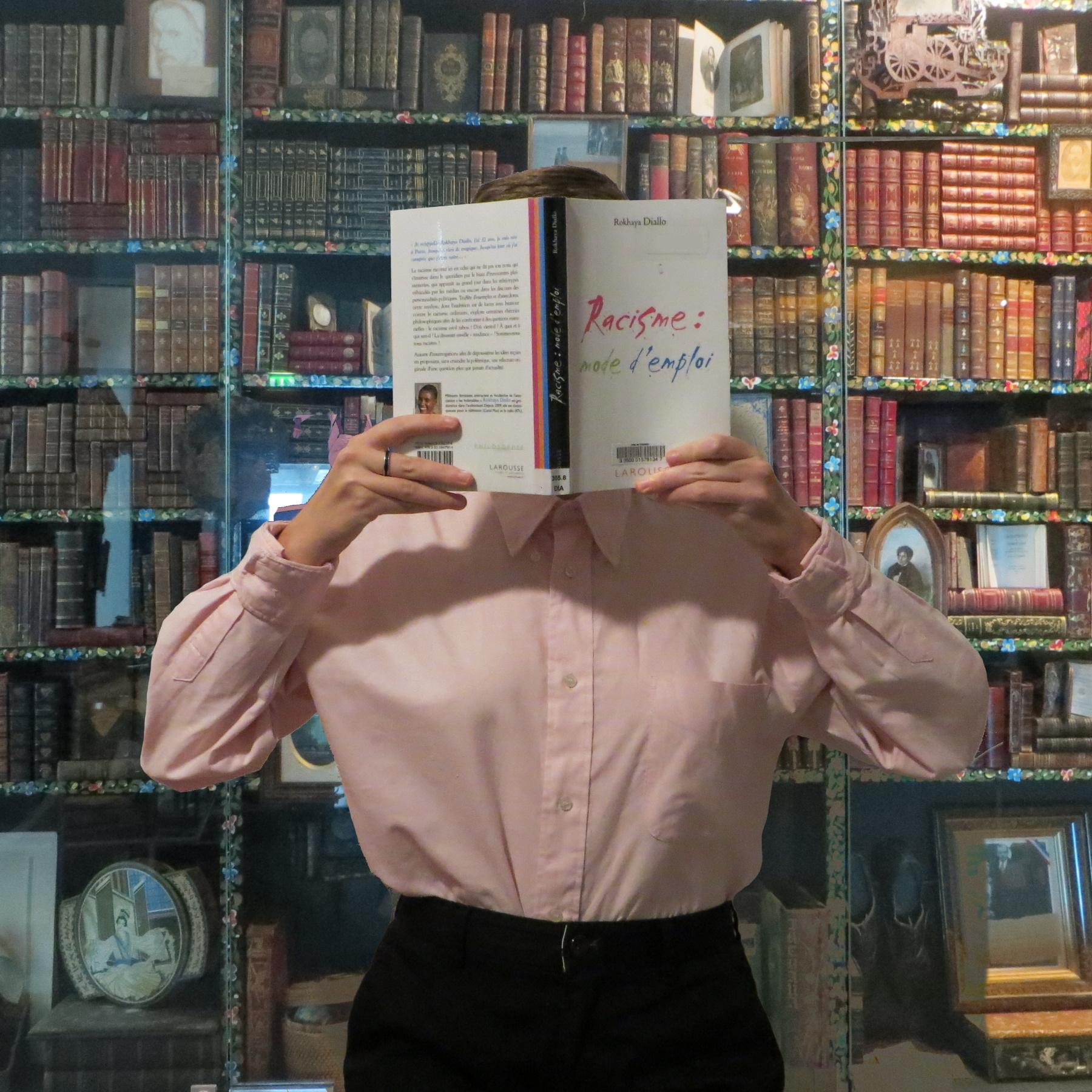 personne en chemise lisant Racisme : mode d'emploi de Rokhaya Diallo dans une bibliothèque pleine de grimoires
