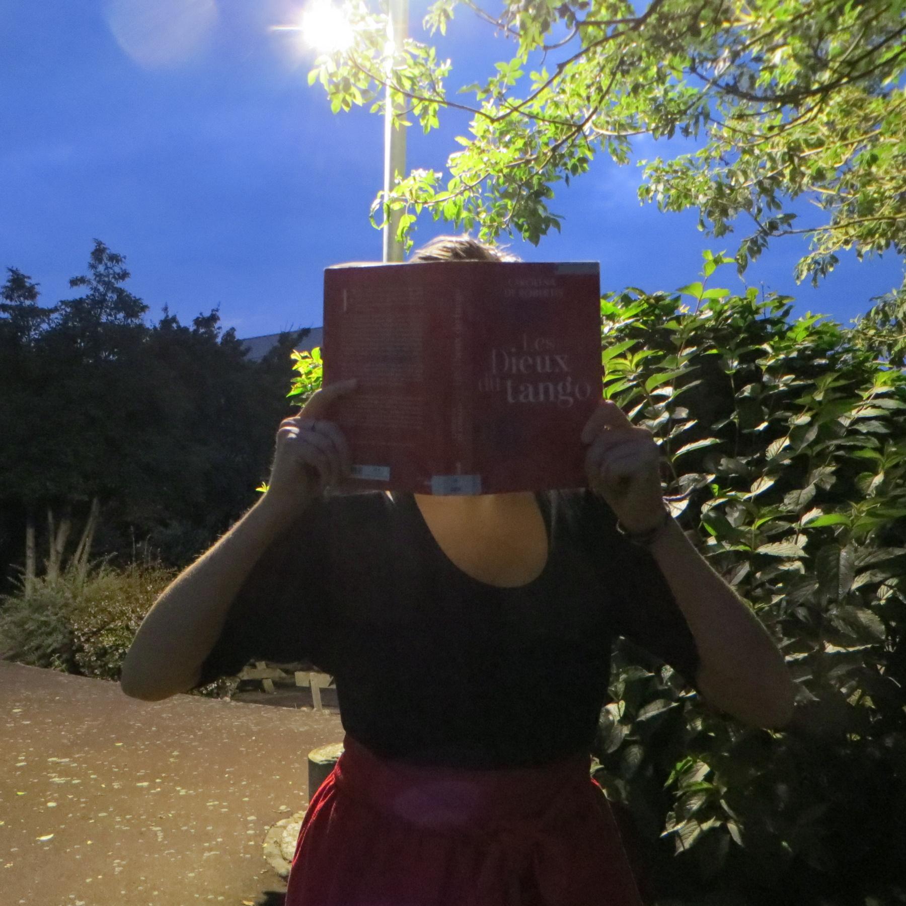 personne en robe rouge et noire lisant Les Dieux du Tango de Carolina de Robertis de nuit, devant un lampadaire