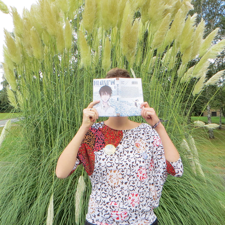 personne en haut à motifs abstraits lisant Eclats d'âme de Yuhki Kamatani devant des plantes d'étang aux feuilles blanches