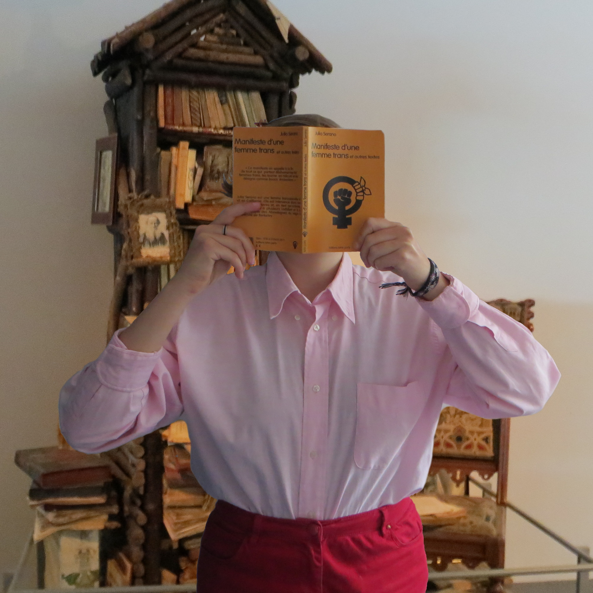 personne en chemise lisant Manifeste d'une femme trans et autres textes de Julia Serano devant une étagère de bois remplie de grimoires